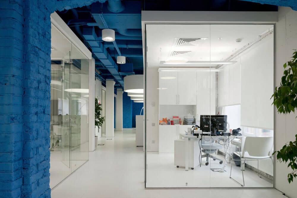 Креативное оформление офиса - синий потолок, белые балки и пол, стеклянные стены офисов - фото 1