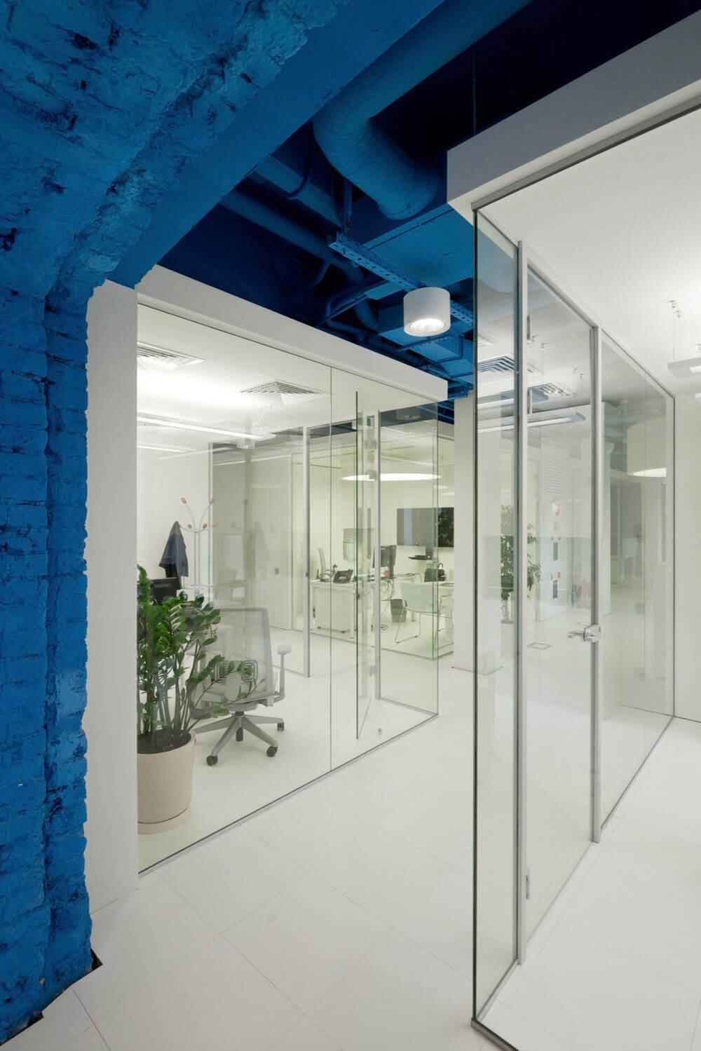 Креативное оформление офиса синий потолок, белые балки и пол, стеклянные стены офисов - фото 4