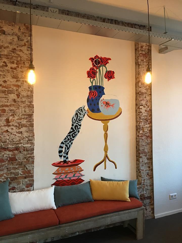 Отделка стен белой штукатуркой с яркими рисунками на фоне неотделанного кирпича