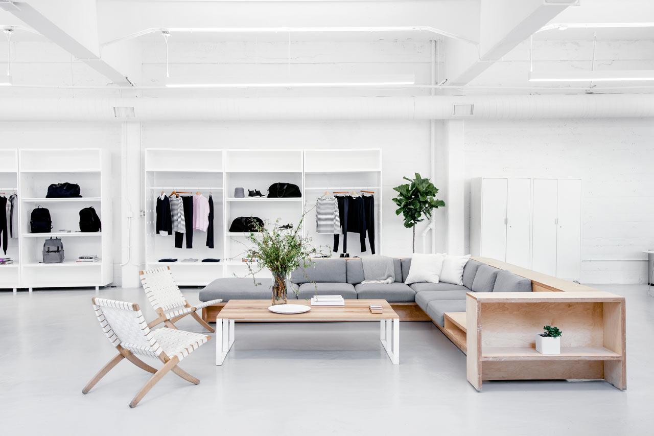 Серый диван  деревянным каркасом в белом интерьере офиса