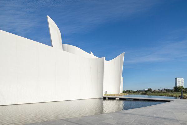 Белый изогнутый фасад музея напоминает поднятый парус