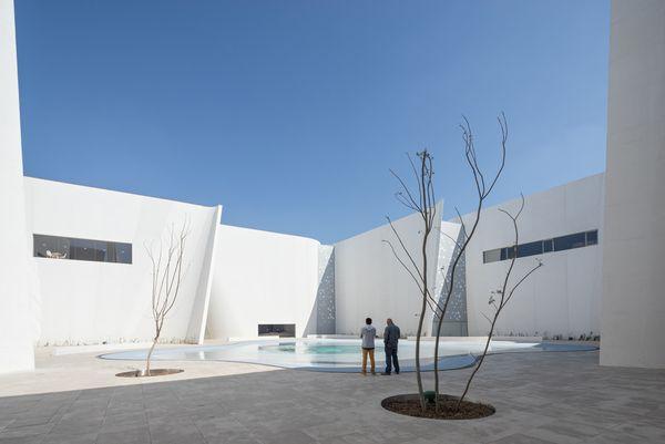 Белый изогнутый фасад: фонтан в образе яйца