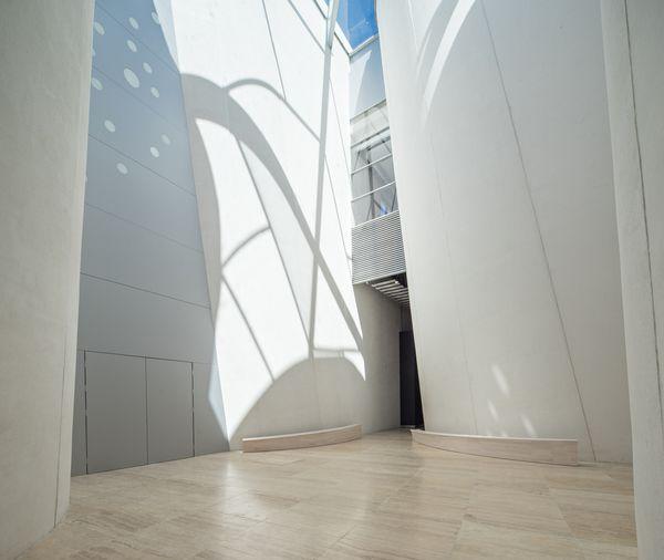 Белый изогнутый фасад построен из сборных железобетонных плит