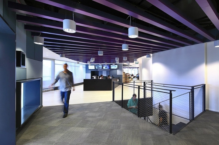 Потолок выполнен из балок фиолетового цвета среди которых спускаются белоснежные подвесные светильники