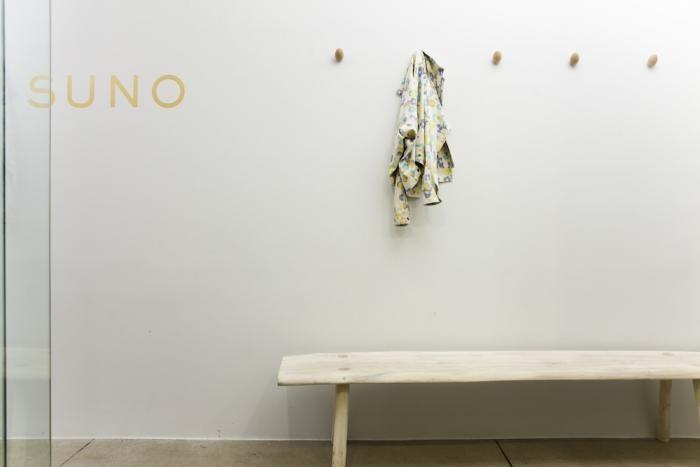 Белая лавочка из натурального дерева в дизайне прихожей офиса