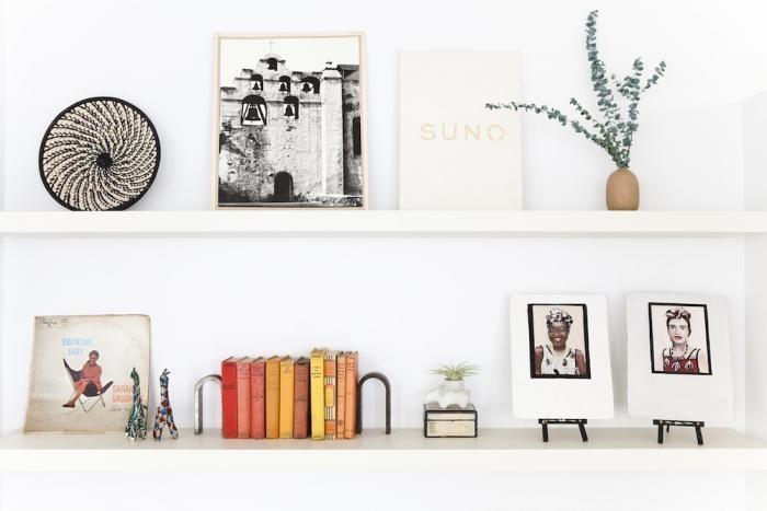 Белые полки с различными предметами декора в дизайне маленького офиса