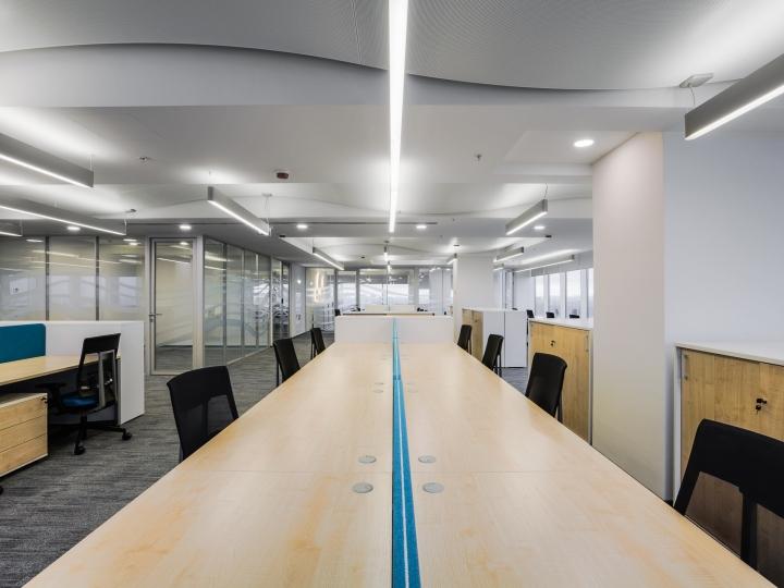 Светлые деревянные столы в интерьере офиса банка