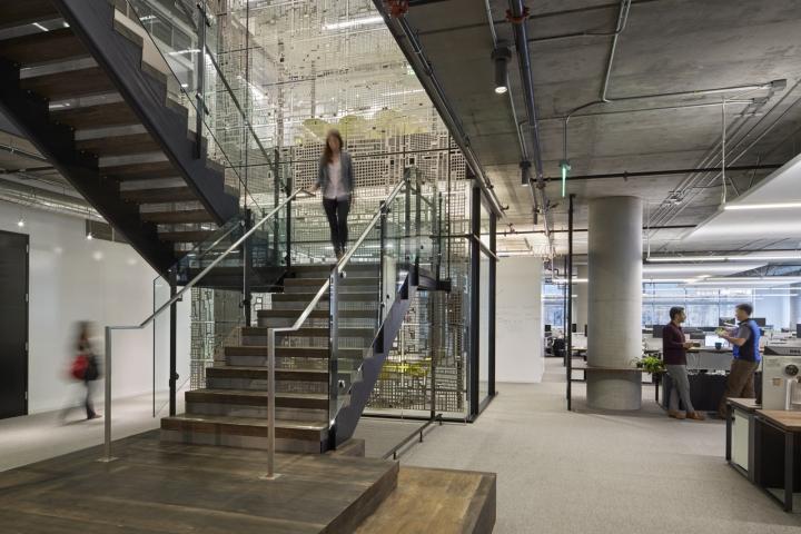 Дизайн офиса в серых тонах: массивная стальная в центре офиса