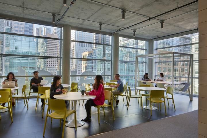 Дизайн офиса в серых тонах: столовая с яркими стульями