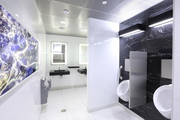 Дизайн освещения офиса от MCM Interiors в Ванкувере - панели с произведениями искусства на стенах