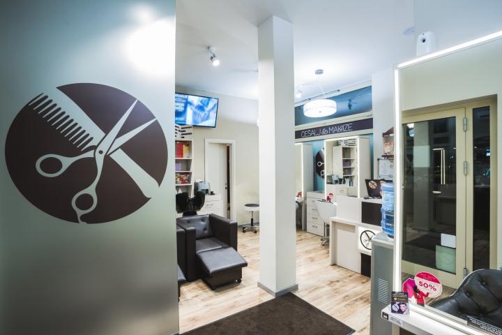 Логотип на стене в дизайне парикмахерской