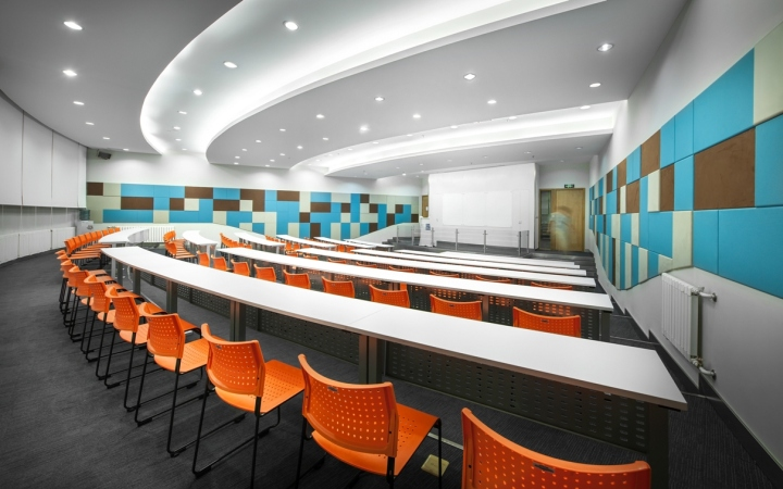 Ярко-оранжевые стулья в интерьере аудитории офиса