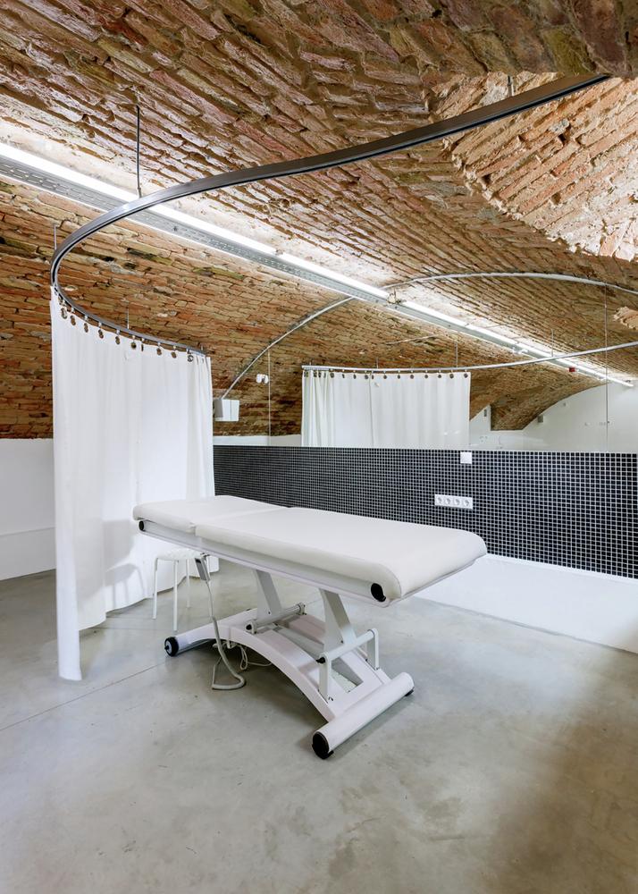 Массажный кабинет за белой шторой в дизайне салона красоты