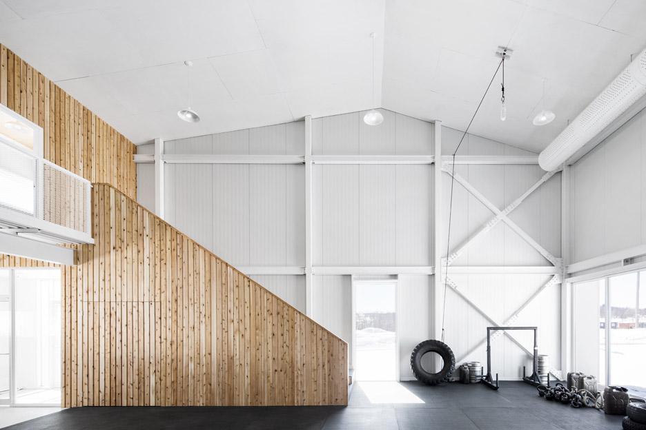 Светлая деревянная отделка лестницы в интерьере фитнес центра