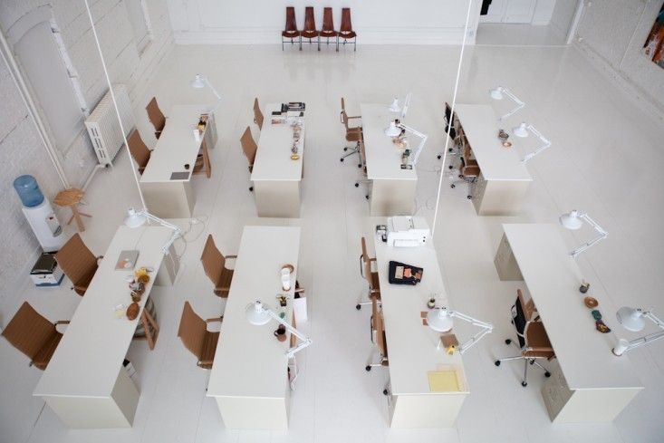 Белые лампы на рабочих столах в интерьере маленького офиса