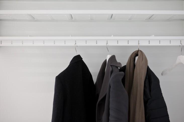 Небольшой белый шкаф для одежды в интерьере маленького офиса
