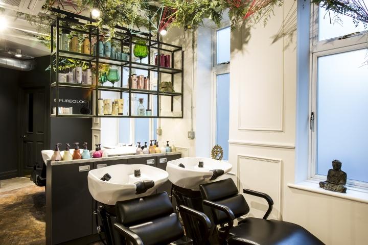 Чёрные полки с косметикой в интерьере парикмахерской