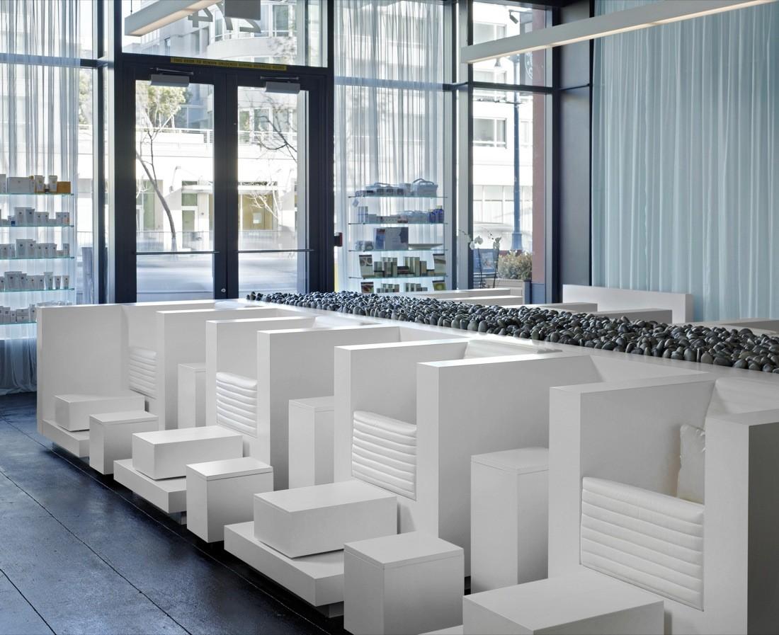 Интерьер спа-салона: «река» из камней между белыми креслами