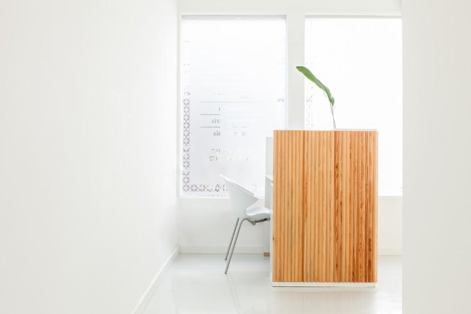 Деревянная отделка стойки регистрации в интерьере стоматологической клиники
