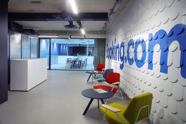 Декорирование белой стены с яркой надписью компании в интерьере комфортного офиса