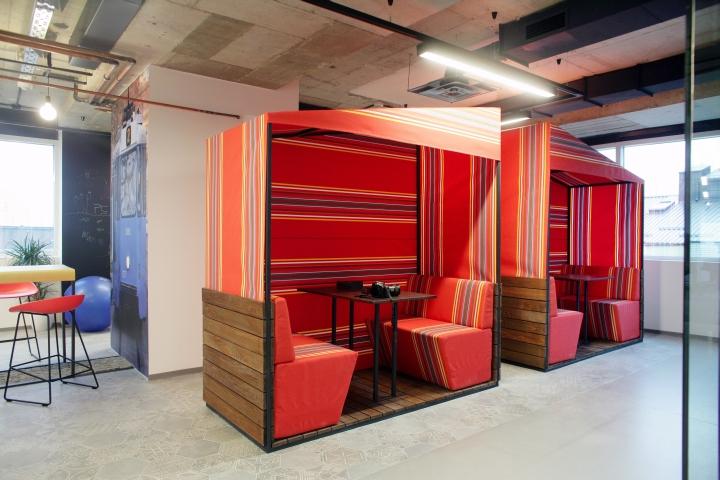 Мягкие диваны с яркой расцветкой в интерьере комфортного офиса