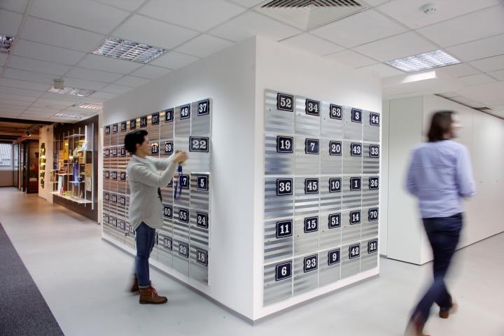 Встроенные серые шкафчики сотрудников в интерьере комфортного офиса