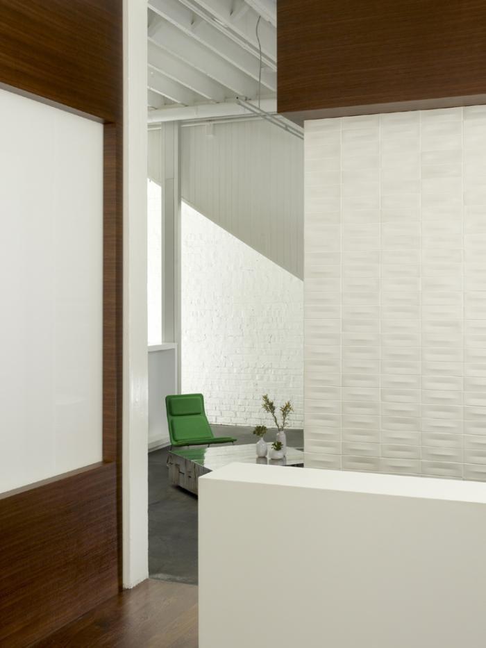 Отделка стены белой керамической плиткой в интерьере комфортного офиса