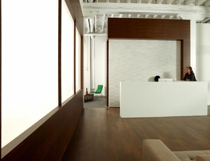 Дизайн белой стойки регистрации в интерьере комфортного офиса