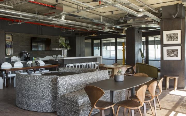 Зона отдыха в коворкинг-офисе - серые диваны и деревянные стулья
