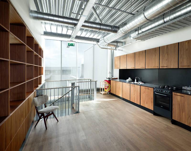 Тёмный кухонный гарнитур в креативном оформлении офиса