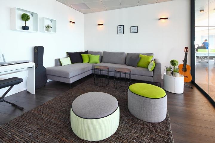 Серый диван с зелёными подушками в креативном дизайне офиса