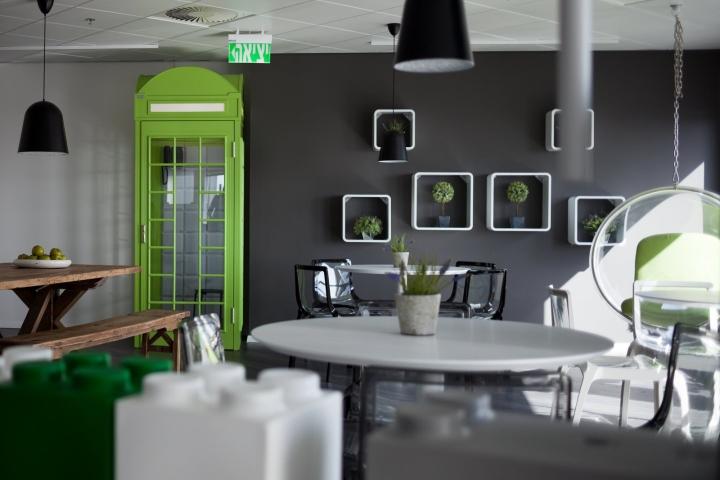 Чёрная стена с оригинальными белыми полками в креативном дизайне офиса