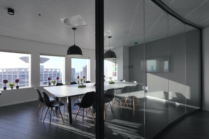 Большой белый стол с чёрными креслами в конференц-зале офиса