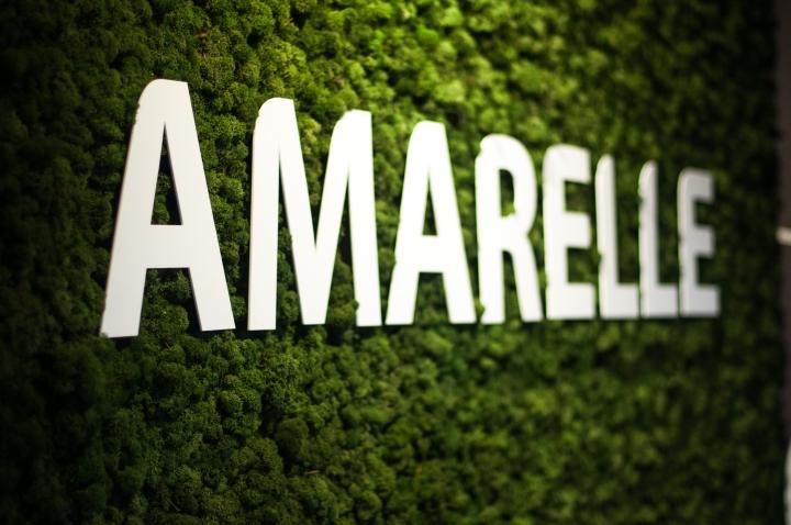 Белый логотип компании на зелёной стене в интерьере креативного офиса