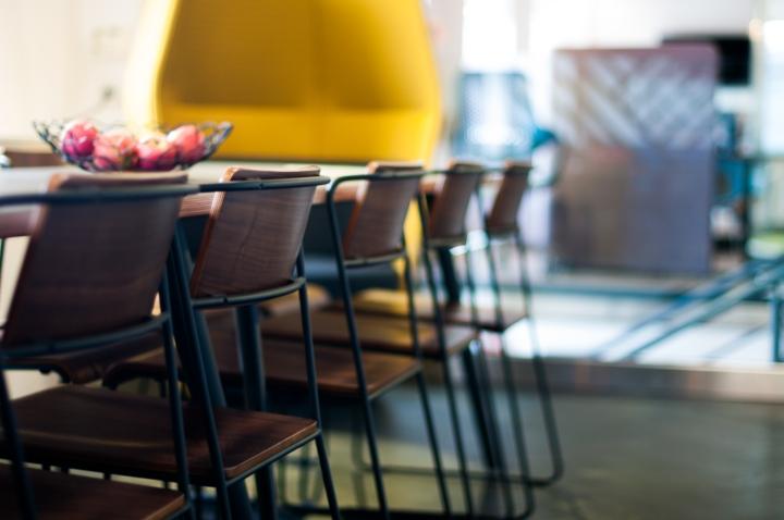 Тёмные деревянные стулья с металлическим каркасом в интерьере креативного офиса