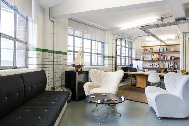 Лофт в интерьере офиса - кирпичная стена и белые дизайнерские кресла
