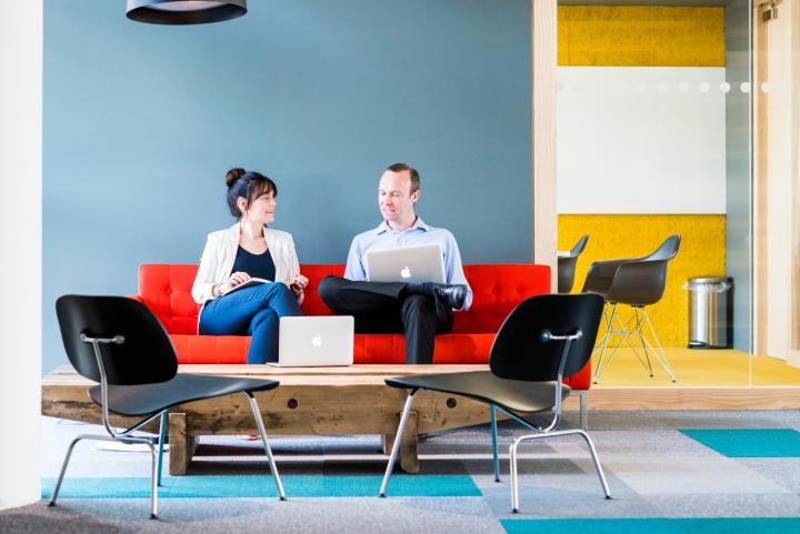 Оформление интерьера офиса: яркий диван и чёрные кресла
