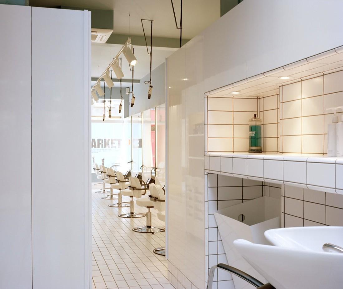 Дизайн парикмахерской: глянцевые стеновые панели по всей длине салона