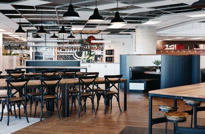 Стильный интерьер офиса - дизайнерская деревянная мебель с металлической фурнитурой в столовой