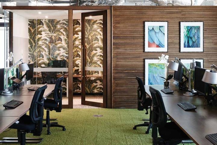 Природные цвета: коричневые деревянные панели на стенах и зеленый ковер в стильном оформлении интерьера офиса