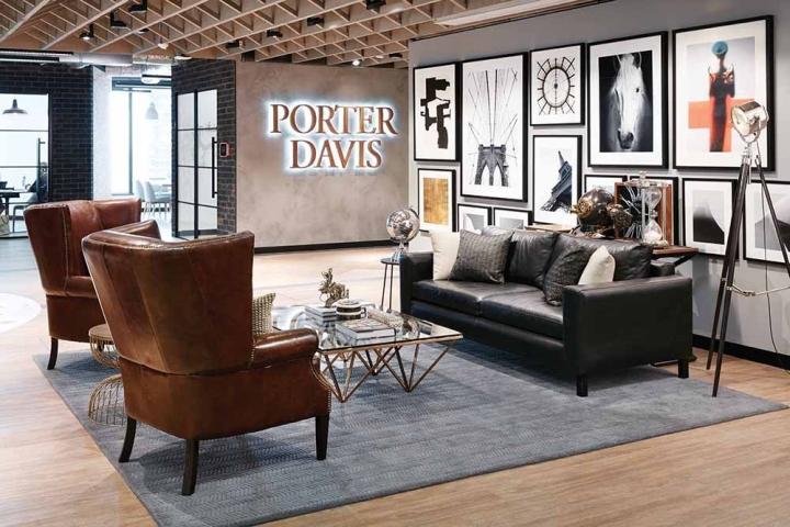 Стильный интерьер офиса - кожаные коричневые кресла и черный диван в зоне отдыха