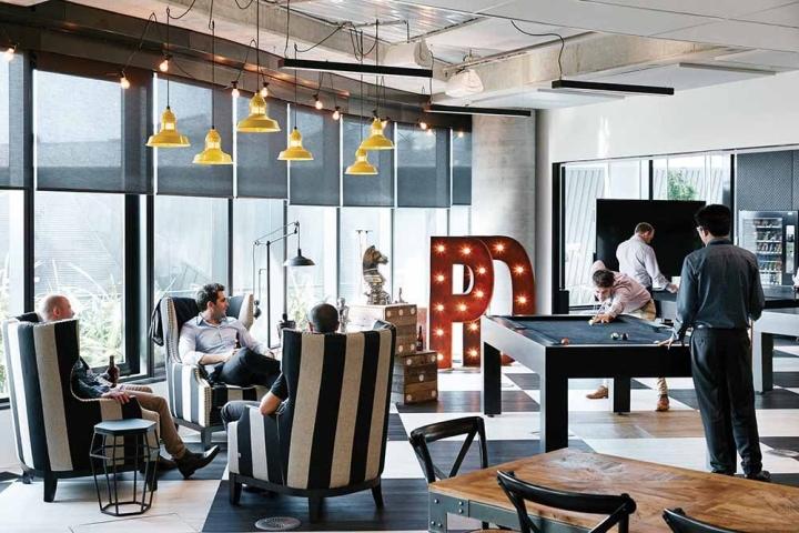 Стильный интерьер офиса - дизайнерские кресла в полоску в зоне отдыха
