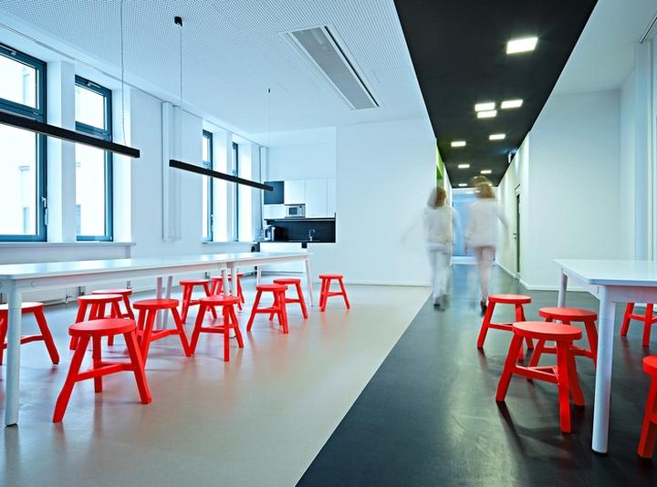 Цветовые акценты в дизайне интерьера офиса в Берлине - яркие красные стульчики