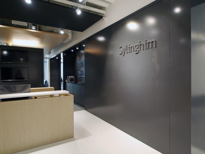 Тёмные цвета в офисе - стойка администратора и логотип компании Sylinghim